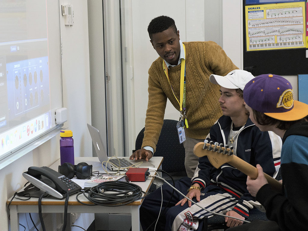students being shown how to use music technology